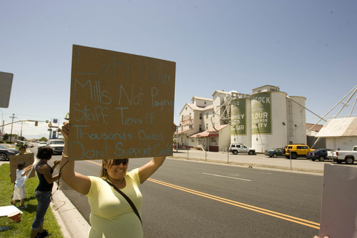 Paul Fraughton   Tribune file photo Marla Rodriguez, whose husband works at the Lehi Roller Mills, holds up a sign at a small protest  across the street from the mills by employees that claim they have not been paid for their work.  Monday, July 9, 2012
