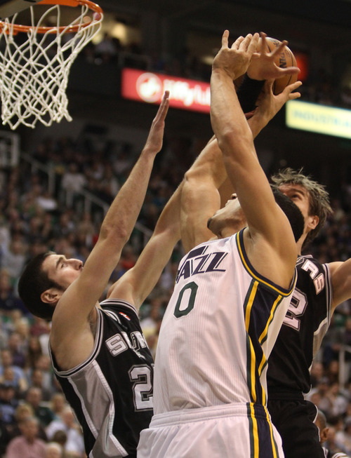 Rick Egan  | The Salt Lake Tribune   Utah Jazz center Enes Kanter (0) is double teamed by San Antonio Spurs point guard Nando de Colo (25) and San Antonio Spurs power forward Tiago Splitter (22) in NBA action, at the Energy Solutions Arena, Wednesday, December 12, 2012.