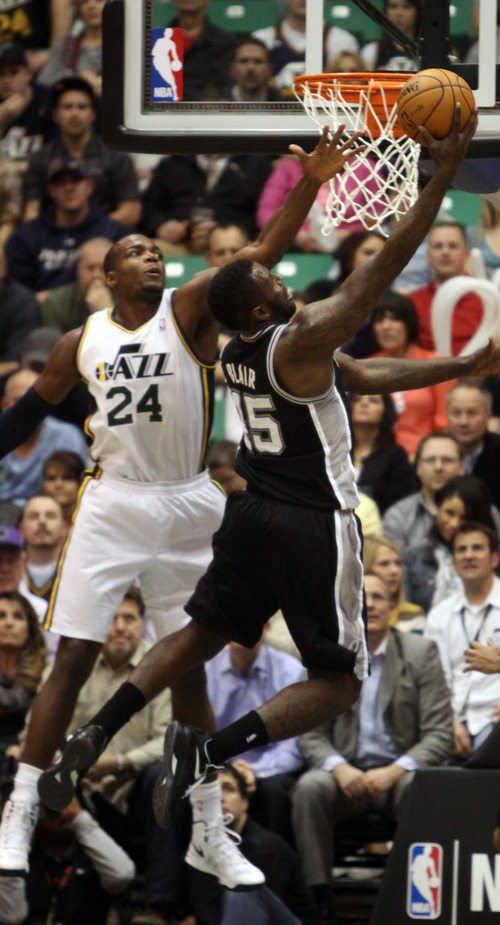 Rick Egan  | The Salt Lake Tribune   Utah Jazz power forward Paul Millsap (24) defends as San Antonio Spurs center DeJuan Blair (45) goes in for a lay-up in NBA action, at the Energy Solutions Arena, Wednesday, December 12, 2012.