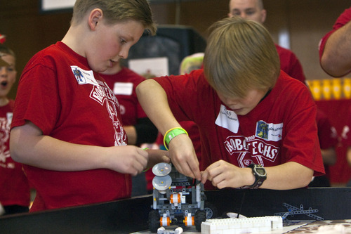 Chris Detrick  |  Tribune file photo Red Cross Robots' Walker Vincent, left, and Jonathan Brucks, prepare a robot for competition during the 2011 FIRST LEGO League Championship at the University of Utah. The 2012 state championship is Jan. 28 but qualifiers begin this weekend.