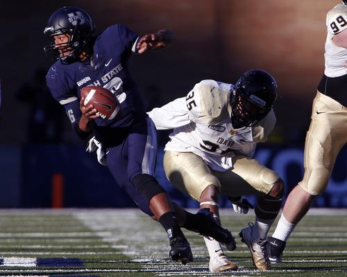 Utah State quarterback Chuckie Keeton (16) is pressured by Idaho linebacker Sua Tuala (35) during the second half of their NCAA college football game in Logan, Utah, Saturday, Nov. 24, 2012. Utah State won 45-9. (AP Photo/Jim Urquhart)