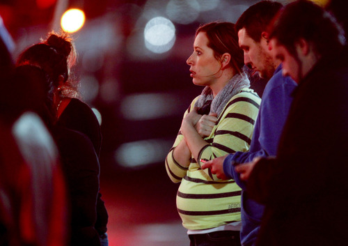 Onlookers observe the scene outside Clackamas Town Center in Portland, Ore., where a shooting occurred Tuesday, Dec. 11, 2012. A gunman opened fire in the Portland, Ore., area shopping mall Tuesday, killing at least one person and wounding an unknown number of others, sheriff's deputies said. (AP Photo/The Oregonian, Bruce Ely)