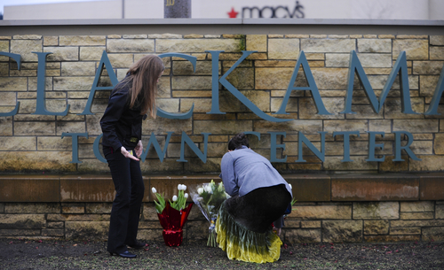 Leslie King, right and Tenille Beseda place flowers Wednesday Dec. 12, 2012, at the entrance to the scene of a multiple shooting yesterday at Clackamas Town Center Mall in Clackamas, Ore.  A gunman who opened fire on shoppers at a Portland mall had no connection to the two people he fatally shot and wanted to kill as many people as possible, police said Wednesday. (AP Photo/Greg Wahl-Stephens)