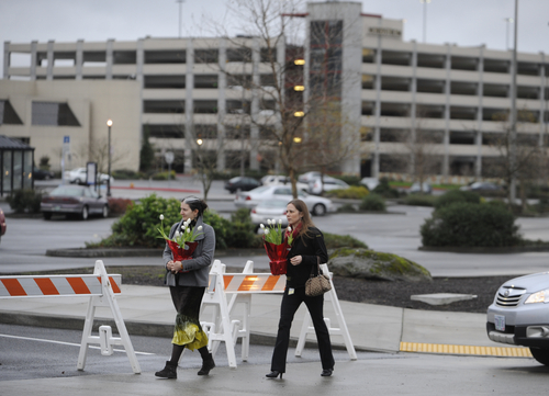 Leslie King, left, and Tenille Beseda carry flowers Wednesday Dec. 12, 2012, to place at the entrance to the scene of a multiple shooting Tuesday at Clackamas Town Center Mall in Clackamas, Ore.   A gunman who opened fire on shoppers at a Portland mall had no connection to the two people he fatally shot and wanted to kill as many people as possible, police said Wednesday. (AP Photo/Greg Wahl-Stephens)