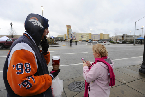 Kyle Price, left, and Angela Price who live directly across from the entrance to the scene of a multiple shooting Tuesday at Clackamas Town Center Mall, take a video to send to friends as they stand across the street in Clackamas, Ore., Wednesday Dec. 12, 2012. (AP Photo/Greg Wahl-Stephens)