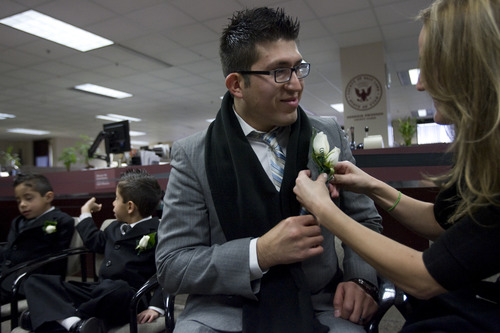 Kim Raff  |  The Salt Lake Tribune J.C. Martinez has a boutonniere fixed to his suit by Wania Rau in the lobby of the Salt Lake County Clerks office before getting married there in Salt Lake City on December 12, 2012. Martinez and his bride Edna Garcia specifically picked the 12/12/12 date to have their wedding ceremony.