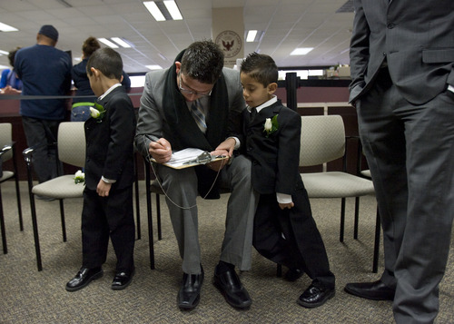 Kim Raff  |  The Salt Lake Tribune (left) Adrian and (right) Anthony Garcia watch as J.C. Martinez fills out a marriage application before getting married at the Salt Lake County Clerk office in Salt Lake City on December 12, 2012. Martinez and his bride Edna Garcia specifically picked the 12/12/12 date to have their wedding ceremony.