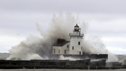 Waves pound a lighthouse on the shores of Lake Erie Tuesday, Oct. 30, 2012, near Cleveland. High winds spinning off the edge of superstorm Sandy took a vicious swipe at northeast Ohio early Tuesday, uprooting trees, cutting power to hundreds of thousands, closing schools and flooding parts of major commuter arteries that run along Lake Erie. (AP Photo/Tony Dejak)