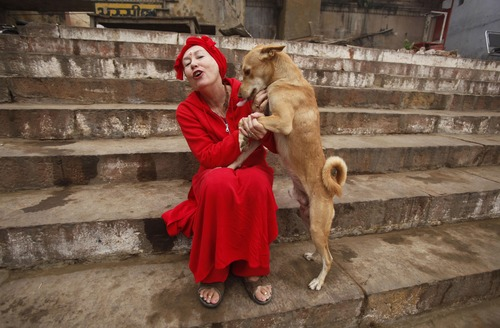Hindu holy woman, Shivani Aum Datri from northern California, USA, plays with a stray dog by the Ganges River in Varanasi, India, Thursday, Dec. 13, 2012. Varanasi is among the world's oldest cities, and millions of Hindu pilgrims gather annually here for ritual bathing and prayers in the Ganges River, considered holiest by Hindus. (AP Photo/Rajesh Kumar Singh)
