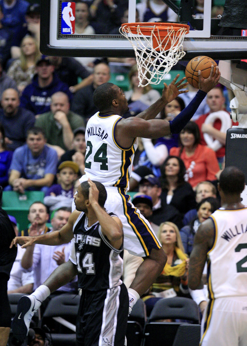 Utah Jazz forward Paul Millsap (24) lays the ball up over San Antonio Spurs guard Gary Neal (14) in the second half during an NBA basketball game Wednesday, Dec.12, 2012, in Salt Lake City. The Jazz defeated the Spurs 99-96. (AP Photo/Rick Bowmer)