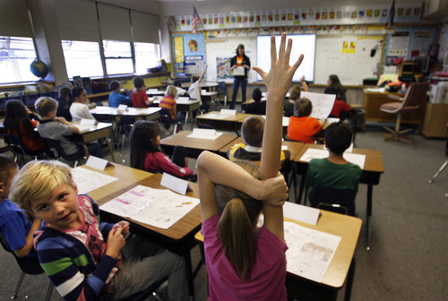 Scott Sommerdorf  |  The Salt Lake Tribune               Ruby Schull raises her hand next to classmate Afton Newell, left, during the United Way and Discover Card visit to their second-grade class at Oquirrh Hills Elementary to teach them about financial literacy through a schoolwide teaching experience, Monday, November 19, 2012.