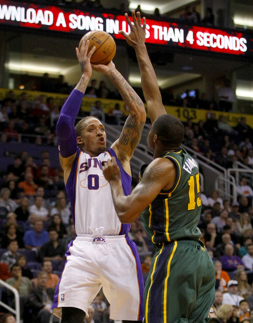 Phoenix Suns forward Michael Beasley (0) shoots over Utah Jazz forward Derrick Favors (15) in the fourth quarter during an NBA basketball game on Friday, Dec. 14, 2012, in Phoenix. The Suns defeated the Jazz 99-84.  (Rick Scuteri/AP Photos)