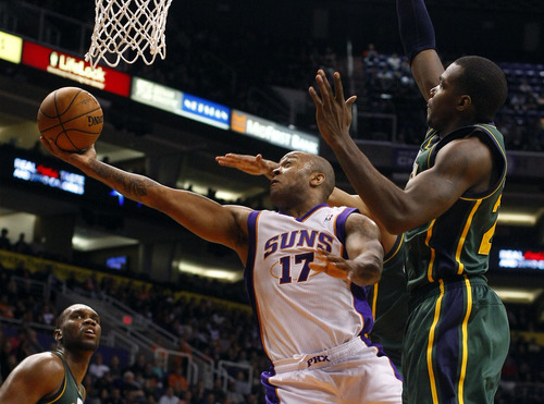 Phoenix Suns guard P.J. Tucker (17) drives and scores against Utah Jazz  forward Paul Millsap (24) in the fourth quarter during an NBA basketball game on Friday, Dec. 14, 2012, in Phoenix. The Suns defeated the Jazz 99-84.  (Rick Scuteri/AP Photos)