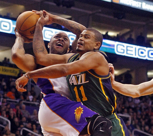Phoenix Suns guard P.J. Tucker (17) gets fouled by Utah Jazz guard Earl Watson (11) in the third quarter during an NBA basketball game on Friday, Dec. 14, 2012, in Phoenix. The Suns defeated the Jazz 99-84.  (Rick Scuteri/AP Photos)