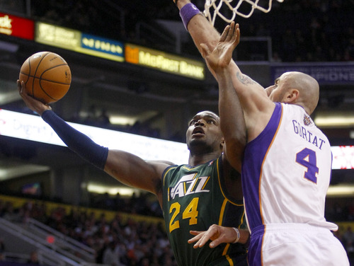 Utah Jazz forward Paul Millsap (24) scores against Phoenix Suns center Marcin Gortat (4) in the first quarter during an NBA basketball game on Friday, Dec. 14, 2012, in Phoenix. (Rick Scuteri/AP Photos)