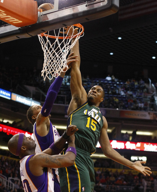 Utah Jazz forward Derrick Favors (15) draws the foul on Phoenix Suns forward Michael Beasley (0) in the second quarter during an NBA basketball game on Friday, Dec. 14, 2012, in Phoenix. (Rick Scuteri/AP Photos)