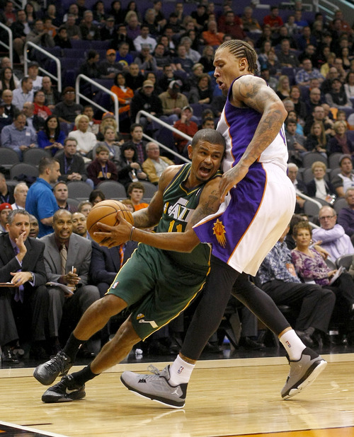 Utah Jazz guard Earl Watson (11) drives on Phoenix Suns forward Michael Beasley (0) in the second quarter during an NBA basketball game on Friday, Dec. 14, 2012, in Phoenix. (Rick Scuteri/AP Photos)