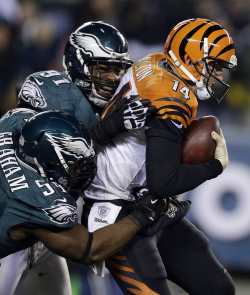 Cincinnati Bengals' Andy Dalton, right, is sacked by Philadelphia Eagles' Brandon Graham, left, and Fletcher Cox in the second half of an NFL football game on Thursday, Dec. 13, 2012, in Philadelphia. (AP Photo/Matt Rourke)