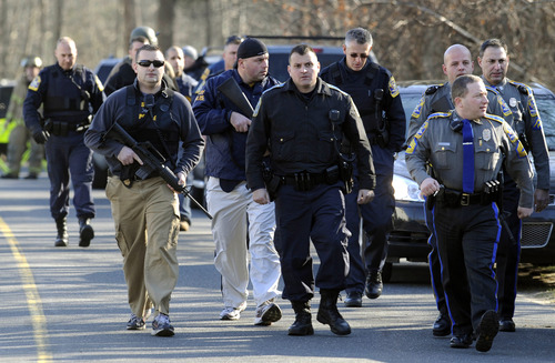 Law enforcement canvass the area following a shooting at the Sandy Hook Elementary School in Newtown, Conn., about 60 miles (96 kilometers) northeast of New York City, Friday, Dec. 14, 2012. An official with knowledge of Friday's shooting said a shooter killed 26 people including 20 children, plus himself.  (AP Photo/Jessica Hill)