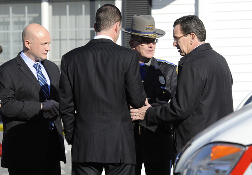 Gov. Dannel P. Malloy, right, talks with officials at a staging area following a shooting at the Sandy Hook Elementary School in Newtown, Conn., about 60 miles (96 kilometers) northeast of New York City, Friday, Dec. 14, 2012. An official with knowledge of Friday's shooting said a gunman killed 26 people including 20 children, plus himself. (AP Photo/Jessica Hill)