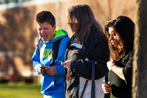 A boy weeps as he is told what happened after being picked up at Reed Intermediate School following a shooting at Sandy Hook Elementary School in Newtown, Connecticut, December 14, 2012. A heavily armed gunman opened fire on school children and staff at a Connecticut elementary school on Friday, killing at least 26 people, including 20 children, plus himself. REUTERS/Lucas Jackson