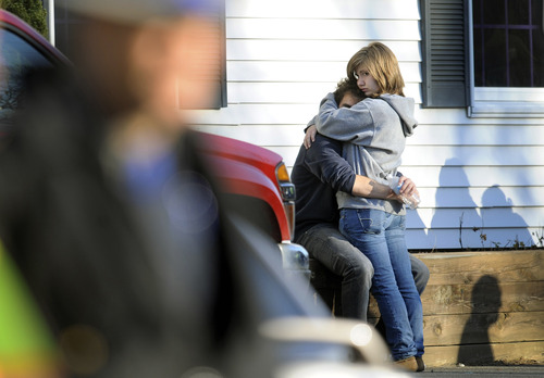 People embrace at a firehouse staging area for family around near the scene of a shooting at the Sandy Hook Elementary School in Newtown, Conn. where authorities say a gunman opened fire, leaving 27 people dead, including 20 children, Friday, Dec. 14, 2012. (AP Photo/Jessica Hill)