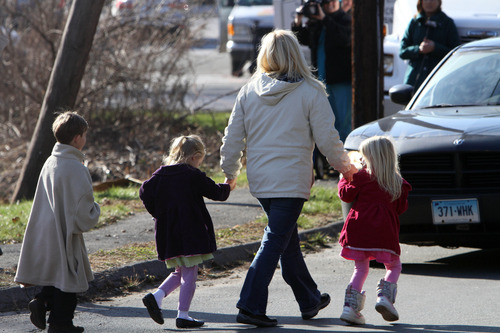 Parents walk away from the Sandy Hook Elementary School with their children following a shooting at the Newtown, Conn. school where authorities say a gunman opened fire, leaving 27 people dead, including 20 children, Friday, Dec. 14, 2012.  (AP Photo/The Journal News, Frank Becerra Jr.) MANDATORY CREDIT, NYC OUT, NO SALES, TV OUT, NEWSDAY OUT; MAGS OUT