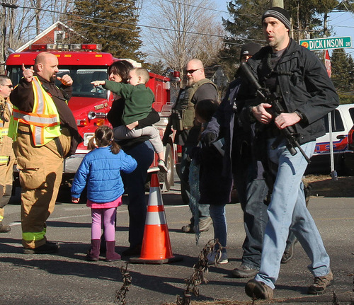A law enforcement official carries a weapon as he walks past firefighters and parents with their children after a shooting at the Sandy Hook Elementary School in Newtown, Conn. on Friday, Dec. 14, 2012. (AP Photo/The Journal News, Frank Becerra Jr.) NYC OUT, NO SALES, TV OUT, NEWSDAY OUT; MAGS OUT; MANDATORY CREDIT: THE JOURNAL NEWS, FRANK BECERRA JR.