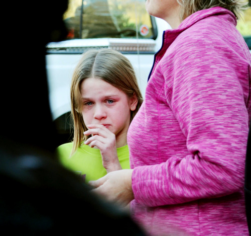 A young girl cires following a shooting at the Sandy Hook Elementary School in Newtown, Conn., about 60 miles (96 kilometers) northeast of New York City, Friday, Dec. 14, 2012. A gunman entered the school Friday morning and killed at least 26 people, including 20 young children. (AP Photo/The New Haven Register, Melanie Stengel)