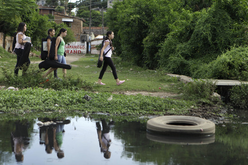 """In this Dec. 11, 2012 photo, young women carry their instruments as they walk alongside a polluted stream to their music practice session with """"The Orchestra of Instruments Recycled From Cateura"""" in Cateura, a vast landfill outside Paraguay's capital of Asuncion, Paraguay. The community of Cateura could not be more marginalized. But the music coming from garbage has some families believing in a different future for their children. (AP Photo Jorge Saenz)"""