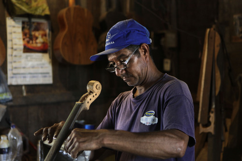 """In this Dec. 11, 2012 photo, Nicolas Gomez makes a violin out of recycled materials at his home in Cateura, a vast landfill outside Paraguay's capital of Asuncion, Paraguay. Gomez, a trash picker and former carpenter, was asked by Favio Chavez, the creator of """"The Orchestra of Instruments Recycled From Cateura,"""" to make instruments out of materials from the dump to help keep the younger kids occupied. """"I only studied until the fifth grade because I had to go work breaking rocks in the quarries,"""" said Gomez, 48. (AP Photo/Jorge Saenz)"""