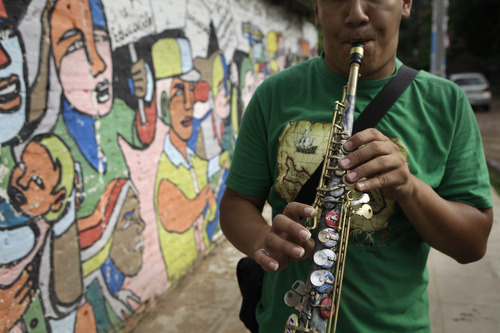 """In this Dec. 11, 2012 photo, Oscar Molina plays a saxophone that was repaired with recycled materials outside the school where he practices with """"The Orchestra of Instruments Recycled From Cateura""""  in Cateura, a vast landfill outside Paraguay's capital of Asuncion, Paraguay.  The community of Cateura could not be more marginalized. But the music coming from garbage has some families believing in a different future for their children. (AP Photo/Jorge Saenz)"""