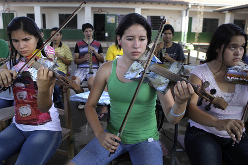 """In this Dec. 11, 2012 photo, Ada Rios, center, plays a violin made of recycled materials during a practice session with """"The Orchestra of Instruments Recycled From Cateura"""" in Cateura, a vast landfill outside Paraguay's capital of Asuncion, Paraguay.  """"The orchestra has given a new meaning to my life, because in Cateura, unfortunately, many young people don't have opportunities to study, because they have to work or they're addicted to alcohol and drugs,"""" Rios said.  (AP Photo/Jorge Saenz)"""