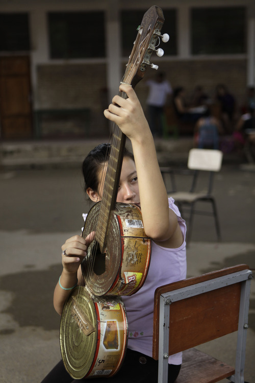 """In this Dec. 11, 2012 photo, Noelia Rios, 12, tunes her guitar made of recycled materials as she practices with """"The Orchestra of Instruments Recycled From Cateura"""" in Cateura, a vast landfill outside Paraguay's capital of Asuncion, Paraguay. Children use instruments fashioned out of recycled materials taken from a landfill where their parents eke out livings as trash-pickers, and about 20 of them regularly perform the music of Beethoven and Mozart, Henry Mancini and the Beatles.  Noelia's 14-year-old sister and 16-year-old aunt also play in the orchestra.  (AP Photo/Jorge Saenz)"""