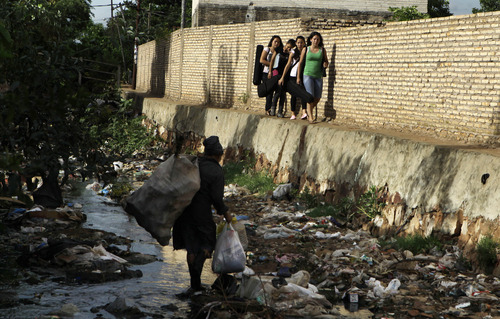 """In this Dec. 11, 2012 photo, young women carry their instruments along the edge of a polluted stream where a woman scavenges for recyclable goods in the garbage, as they head to their practice session with """"The Orchestra of Instruments Recycled From Cateura,"""" in Cateura, a vast landfill outside Paraguay's capital of Asuncion, Paraguay.  The community of Cateura could not be more marginalized. But the music coming from garbage has some families believing in a different future for their children. (AP Photo Jorge Saenz)"""