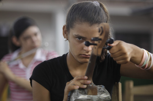 """In this Dec. 11, 2012 photo, Tania Vera, 15, tunes her violin during a practice session with """"The Orchestra of Instruments Recycled From Cateura"""" in Cateura, a vast landfill outside Paraguay's capital of Asuncion, Paraguay. I never thought my dreams would become reality,"""" said Vera, who lives in a wooden shack by a contaminated stream. Her mother has health problems, her father abandoned them, and her older sister left the orchestra after becoming pregnant. Tania, though, keeps to her goal of becoming a veterinarian as she keeps up with the music. (AP Photo/Jorge Saenz)"""