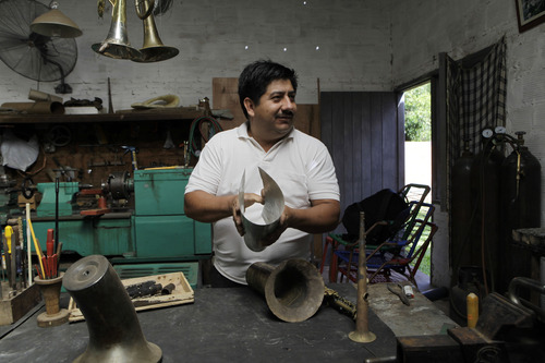"""In this Dec. 8, 2012 photo, Tito Romero demonstrates how he makes a trumpet with recycled metal in his workshop at his home in Capiata, Paraguay. Romero was repairing damaged trumpets in a shop outside Asuncion until Favio Chavez, the creator of  """"The Orchestra of Instruments Recycled From Cateura,"""" asked him to turn galvanized pipe and other pieces of metal into flutes, clarinets and saxophones for his students. (AP Photo/Jorge Saenz)"""