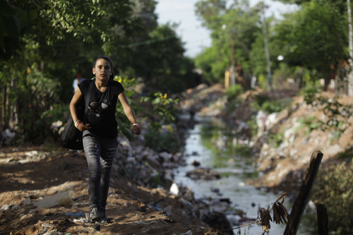 """In this Dec. 11, 2012 photo, Tania Vera, 15, walks from her home alongside a polluted stream to practice with """"The Orchestra of Instruments Recycled From Cateura"""" in Cateura, a vast landfill outside Paraguay's capital of Asuncion, Paraguay. I never thought my dreams would become reality,"""" said Vera, who lives in a wooden shack by a contaminated stream. Her mother has health problems, her father abandoned them, and her older sister left the orchestra after becoming pregnant. Tania, though, keeps to her goal of becoming a veterinarian as she keeps up with the music. (AP Photo/Jorge Saenz)"""