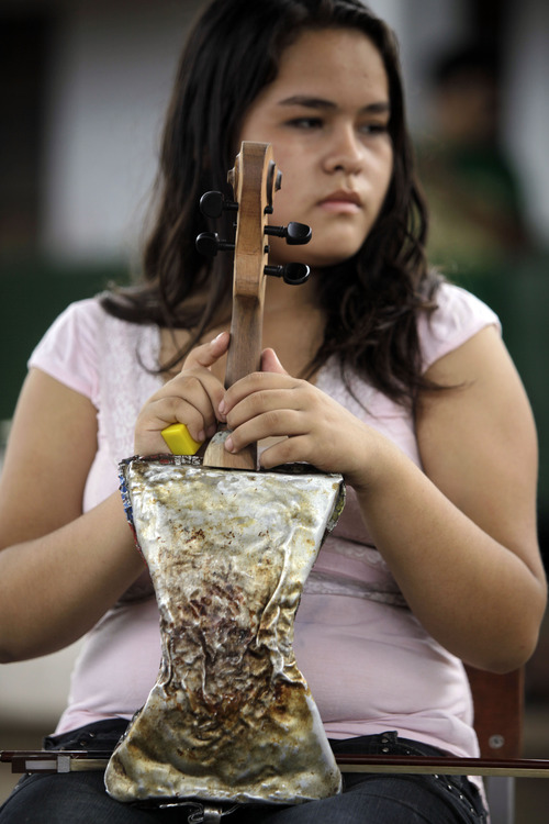 """In this Dec. 11, 2012 photo, musician Maria Rios, 16, holds her violin made of recycled materials before practicing with """"The Orchestra of Instruments Recycled From Cateura""""  in Cateura, a vast landfill outside Paraguay's capital of Asuncion, Paraguay.  """"My mother signed me up in teacher Chavez's school three years ago. I was really bothered that she hadn't asked me first, but today I'm thankful because she put my name in as someone who wanted to learn violin,"""" Maria said. (AP Photo/Jorge Saenz)"""
