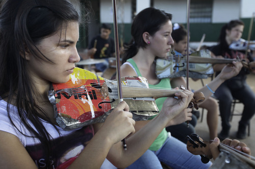 """In this Dec. 11, 2012 photo, Ana Meza, 16, plays a violin made of recycled materials as she attends a practice session with """"The Orchestra of Instruments Recycled From Cateura""""  in Cateura, a vast landfill outside Paraguay's capital of Asuncion, Paraguay.  After years of practice, the youngsters of """"The Orchestra of Instruments Recycled From Cateura"""" have begun to perform internationally, with sponsors paying their way to places like Brazil, Panama and Colombia.  They hope to play at an exhibit opening next year in their honor at the Musical Instrument Museum in Phoenix, Arizona. (AP Photo/Jorge Saenz)"""