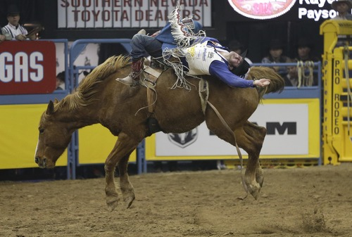 Kaycee Feild of Payson, Utah, rides in the bareback riding competition of the National Finals Rodeo, Friday, Dec. 14, 2012, in Las Vegas. (AP Photo/Julie Jacobson)