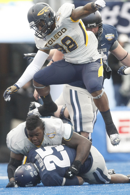 Chris Detrick  |  The Salt Lake Tribune Utah State Aggies running back Kerwynn Williams (25) is tackled by Toledo Rockets defensive tackle Elijah Jones (8) as Toledo Rockets linebacker Robert Bell (38) jumps over them during the second quarter of the Famous Idaho Potato Bowl at Bronco Stadium Saturday December 15, 2012.  At the end of the first half the Aggies were winning, 10-6.