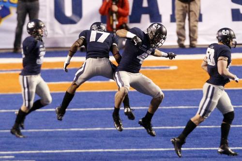 Chris Detrick  |  The Salt Lake Tribune Utah State Aggies wide receiver Matt Austin (4) and cornerback Will Davis (17) celebrate during the Famous Idaho Potato Bowl at Bronco Stadium Saturday December 15, 2012.  The Aggies beat the Rockets, 41-15.