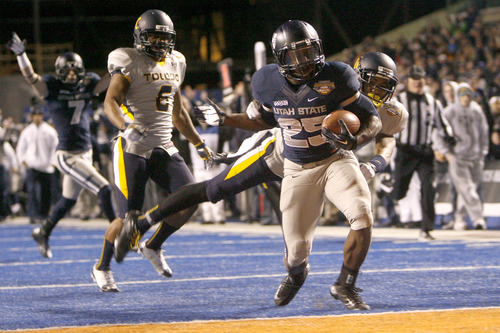 Chris Detrick  |  The Salt Lake Tribune Utah State Aggies running back Kerwynn Williams (25) scores a touchdown past Toledo Rockets defensive back Cheatham Norrils (11) during the fourth quarter of the Famous Idaho Potato Bowl at Bronco Stadium Saturday December 15, 2012.  The Aggies beat the Rockets, 41-15.