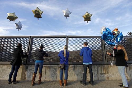 Suada Likovic, 24, from left, Chelsea Crain, 23, Kristin Hoyt, 18, Jeffrey Hoyt, 16, and Linda Hoyt, all of Danbury, Conn., tie balloons to an overpass up the road from the Sandy Hook Elementary School, Saturday, Dec. 15, 2012, in Newtown, Conn. The massacre of 26 children and adults at Sandy Hook Elementary school elicited horror and soul-searching around the world even as it raised more basic questions about why the gunman, 20-year-old Adam Lanza, would have been driven to such a crime and how he chose his victims. (AP Photo/David Goldman)