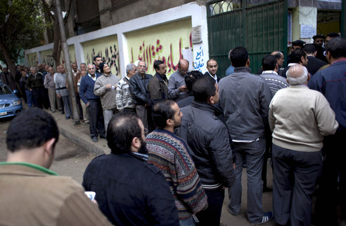 Egyptian voters line up outside a polling center for a referendum on a disputed constitution drafted by Islamist supporters of President Mohammed Morsi, in Cairo, Egypt, Saturday, Dec. 15, 2012.(AP Photo/Nasser Nasser)