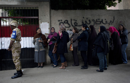An Egyptian soldier stands guard outside a polling center as women stand in line to cast their votes during a referendum on a disputed constitution drafted by Islamist supporters of President Mohammed Morsi, in Cairo, Egypt, Saturday, Dec. 15, 2012. Egyptians were voting on Saturday on a proposed constitution that has polarized their nation, with Morsi and his Islamist supporters backing the charter, while liberals, moderate Muslims and Christians oppose it. (AP Photo/Nasser Nasser)