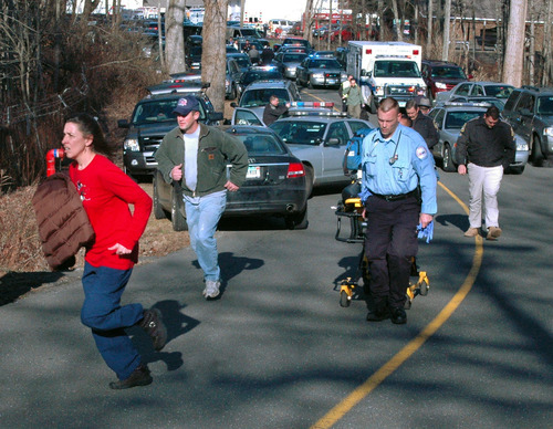 In this photo provided by the Newtown Bee, paramedics and others rush toward Sandy Hook Elementary School in Newtown, Conn., where authorities say a gunman opened fire, killing 26 people, including 20 children, Friday, Dec. 14, 2012. (AP Photo/Newtown Bee, Shannon Hicks) MANDATORY CREDIT: NEWTOWN BEE, SHANNON HICKS