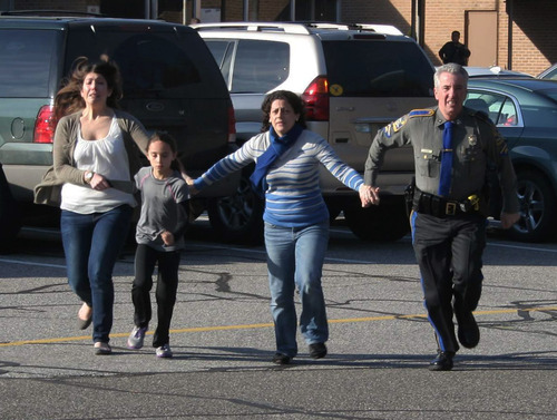 In this photo provided by the Newtown Bee, a police officer leads two women and a child from Sandy Hook Elementary School in Newtown, Conn., where a gunman opened fire, killing 26 people, including 20 children, Friday, Dec. 14, 2012. (AP Photo/Newtown Bee, Shannon Hicks) MANDATORY CREDIT: NEWTOWN BEE, SHANNON HICKS