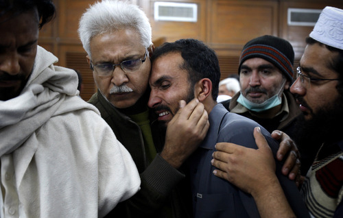 A Pakistani man comforts another mourning over the death of his relative, a victim of a rocket attack by militants, at a local hospital in Peshawar, Pakistan on Saturday, Dec. 15, 2012. Militants fired three rockets at an airport in the northwestern Pakistani city of Peshawar on Saturday night, killing several people and wounding dozens, officials said. (AP Photo/Mohammad Sajjad)